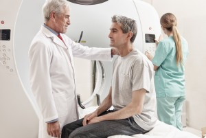 Senior male doctor explaining CT scanner exam to man in 40s. Fem